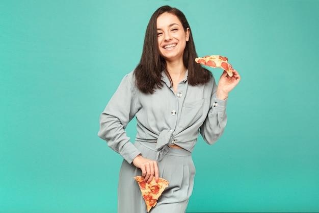 かわいい女性の写真は、ピザ、ジャンクフードで遊んでいます。灰色のシャツ、孤立したターコイズ色の背景を着ています。