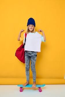 子供の頃のライフスタイルを手にスケートボードでポーズをとって白いtシャツを着たかわいい女の子の写真