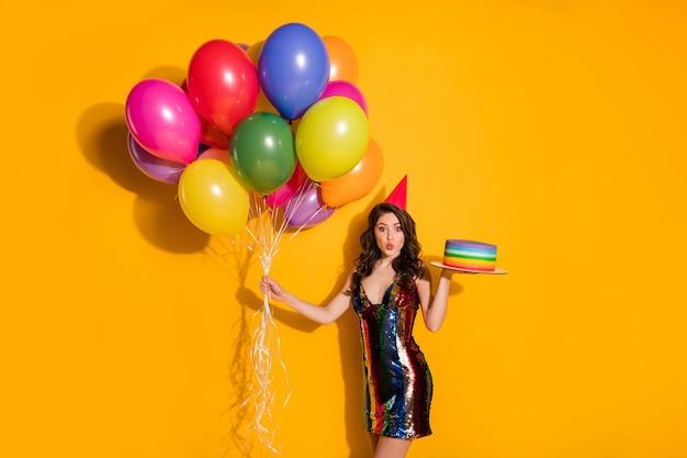 생일 모자를 쓴 귀여운 소녀의 사진은 기념일을 축하하는 케이크 풍선을 들고 밝은 색 배경 위에 격리된 미니 짧은 치마를 입고 공기 키스를 보냅니다.