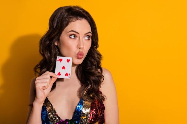 Фотография милой милой красивой девушки с надутыми губами, пухлым взглядом, играющими сердечками, карта, носящая глянцевую юбку, изолированную на ярком фоне цвета блеска