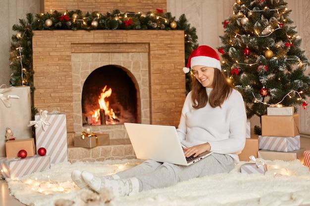 귀여운 멋진 매력적인 매력적인 여자가 그녀의 노트북과 함께 새해 전날 화상 통화를 갖는 캐주얼 흰색 스웨터와 빨간 모자를 쓰고, 매력적인 미소로 장치의 카메라를 바라 봅니다.
