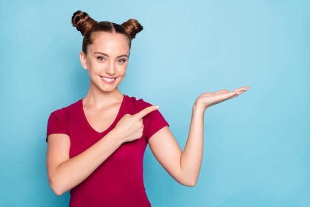 Фотография милой, довольно милой привлекательной подруги, указывающей на ее руку, держащую пустое место, где ваша реклама должна зубасто улыбаться, изолированная на синей пастельной стене