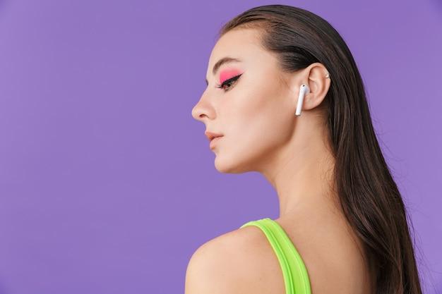 イヤポッドを使用して下向きに明るい化粧をしたかわいい真面目な女性の写真