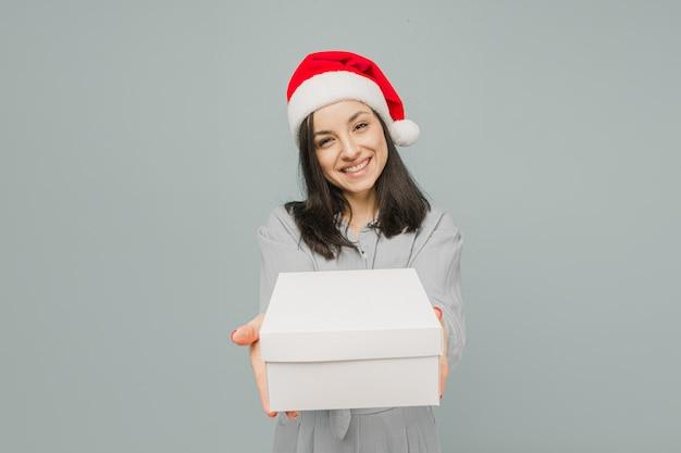 Фото милой улыбающейся женщины в рождественской шляпе, дающей подарок. носит серую рубашку, изолированный серый цвет фона.