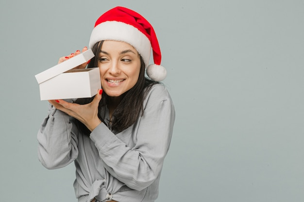 Фото милой улыбающейся женщины в новогодней шапке любопытно открывает подарок. носит серую рубашку, изолированный серый цвет фона.