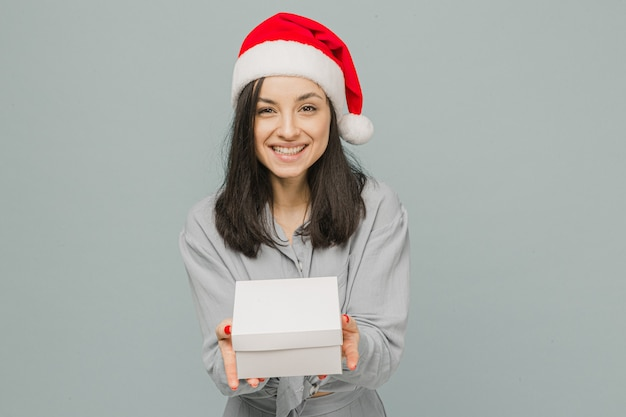 Фото милой улыбающейся женщины в рождественской шляпе дает подарок. носит серую рубашку, изолированный серый цвет фона.
