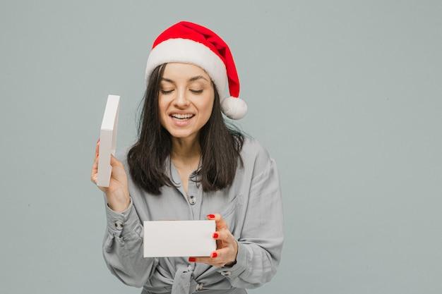 Фото милой улыбающейся женщины в новогодней шапке открывает настоящее. носит серую рубашку, изолированный серый цвет фона.