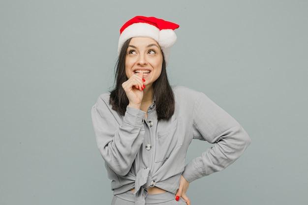Любопытно выглядит фото милой улыбающейся самки в новогодней шапке. носит серую рубашку, изолированный серый цвет фона.