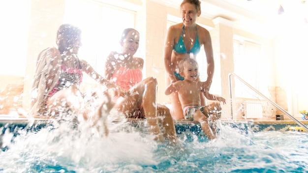 プールに座って水をはねかける若い母親と姉とかわいい幼児の男の子の写真。家族で遊んだり、プールで楽しんだりする