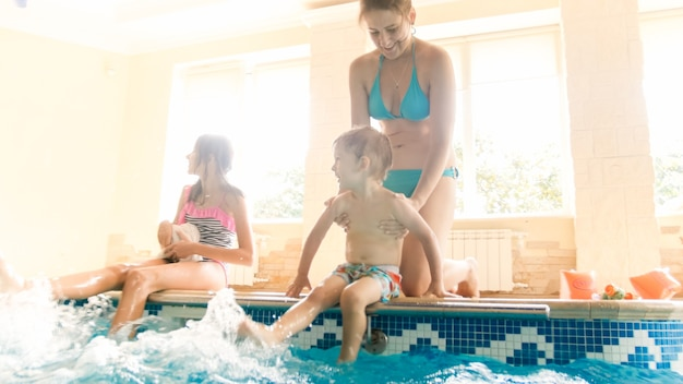 어린 엄마와 누나가 수영장에 앉아 물을 튀기고 있는 귀여운 어린 소년의 사진. 수영장에서 놀고 즐거운 가족