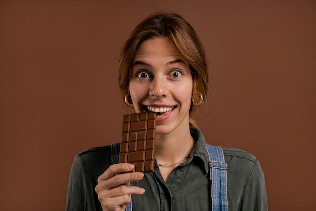 Фотография милой женщины-фермера, с удовольствием ест темный шоколад. женщина носит джинсовые комбинезоны, изолированный коричневый цвет фона.