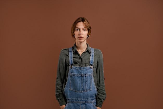 Фото милой женщины-фермера стоит с серьезным лицом. женщина носит джинсовые комбинезоны, изолированный коричневый цвет фона.