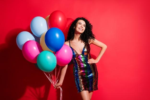 Фотография симпатичной молодой девушки держит много воздушных шаров, смотрит вверх пустое пространство, носит глянцевое короткое платье, изолированное ярким красным цветом фона
