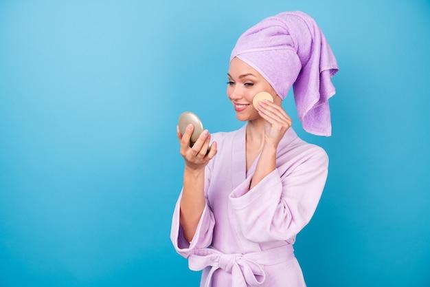 かわいい若い女性の写真ホールドルックミラーコットンスポンジ晴れやかな笑顔着用バイオレットタオルターバンバスローブ分離された青い色の背景