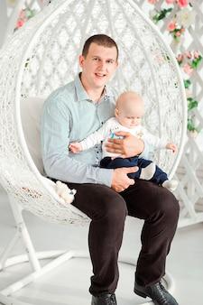Фото папы и сына сидят в модном круглом кресле