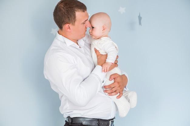 お父さんの写真は彼の腕の中で小さな息子を保持し、青色の背景にポーズ