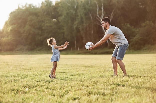 娘が背景の美しい草や森にボールを投げているお父さんの写真。