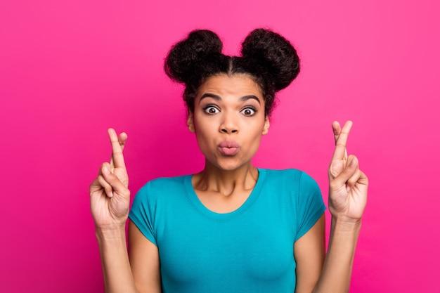 ピンクの背景に暗い肌の女性のクロス指の写真