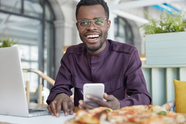 暗い肌の豊かなオフィスマネージャーの写真は、メッセージの送信に最新の携帯電話を使用し、ポータブルラップトップコンピューターで動作します