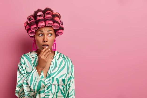 肌の色が濃い女性の写真は、髪をカールさせ、カーラーを着用し、自宅で髪型を作り、開いた口に手を保ち、カジュアルな服を着て、ピンクの壁にポーズをとり、空白の空きスペースを脇に置きます