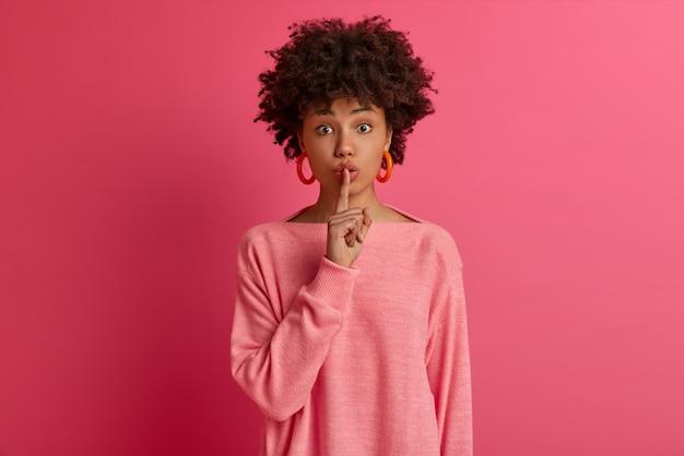 浅黒い肌の女性の写真は人差し指を唇に押し付け、沈黙を保つことを要求し、不思議なことに身をかがめ、誰かのために秘密を準備し、身振りをし、カジュアルな服を着て、ピンクの壁に隔離します