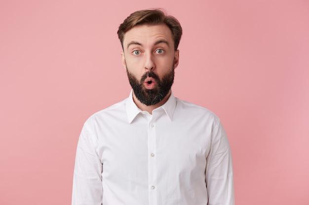 ぼんやりしたハンサムなあごひげを生やした男の写真は、白いシャツを着て、衝撃的なニュースを聞くことを期待していませんでした。ピンクの背景の上に分離された大きく開いた口でカメラを見てください。