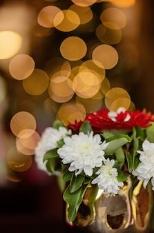 새 해 나무의 bokeh와 배경에 꽃으로 장식 된 크리스마스 꽃병의 사진