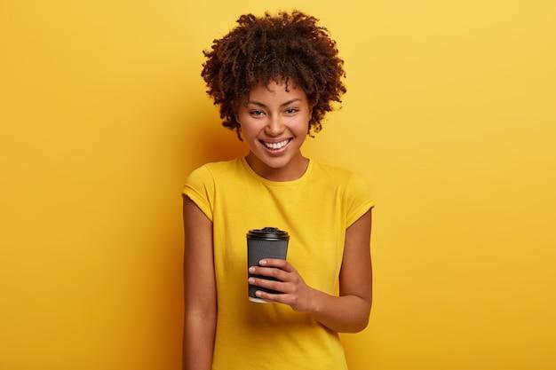 喜んでいるアフリカ系アメリカ人の女性の写真は、持ち帰り用のコーヒーを持ち、芳香のある飲み物を楽しみ、歯を見せる笑顔、白い歯、カジュアルな黄色のtシャツを着ています