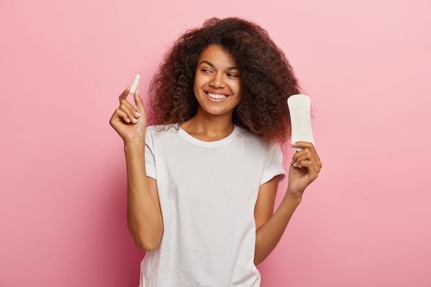 喜んでいるアフリカ系アメリカ人の女性の写真は、ピンクの壁に隔離された白いtシャツを着たタンポンと生理用ナプキンを持っています。女性、月経前症候群