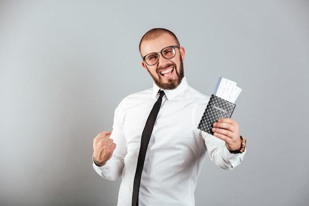 Фото восторге бизнесмена, радуясь его отпуск, держа паспорт и билеты, изолированных на серую стену