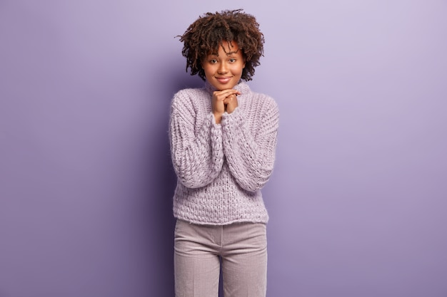 На фото восхищенная симпатичная женщина держит руки под подбородком, радостно улыбается, внимательно слушает приятную информацию, носит зимний фиолетовый свитер, позирует в помещении. концепция выражения лица.