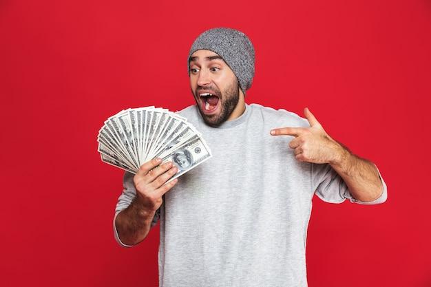 Фотография восхищенного парня 30-х годов в повседневной одежде, радующегося и держащего наличные деньги изолированными