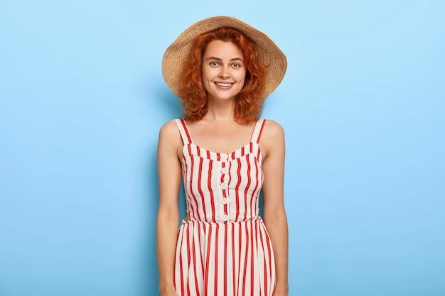 喜んでいる赤い髪の女性の写真は麦わら帽子と夏の縞模様のサラファンを着ています