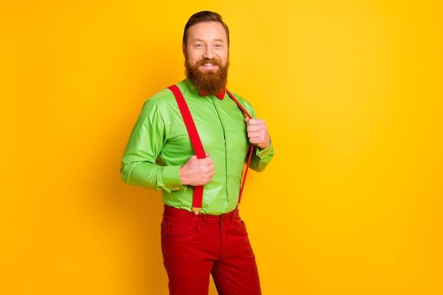 Фото восхищенного рыжего парня, зубастого улыбающегося, элегантного фанк-вечеринки, взгляд, держаться за руки, подтяжки, носить ярко-зеленую рубашку, красные брюки с галстуком-бабочкой, изолированные на желтый
