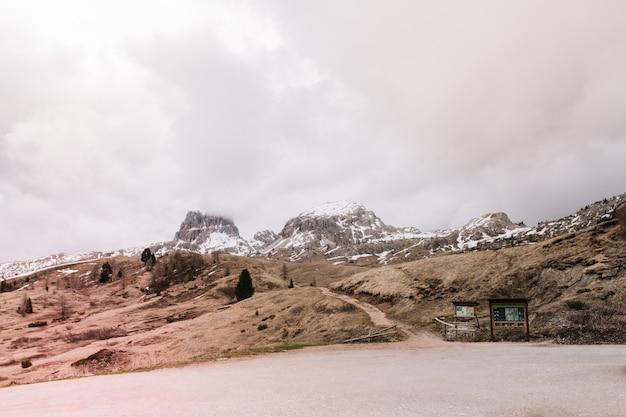 遠くの山々とどんよりした空とイタリアの人けのない風景の写真