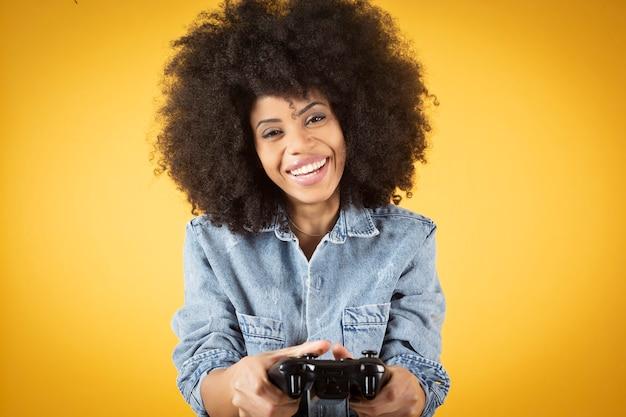 孤立した黄色の背景を再生して楽しんでいるデニムジーンズを身に着けている歯を見せて笑っているディルドクレイジー興奮した楽しい笑顔の写真
