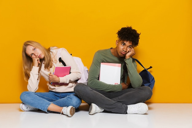 黄色の背景の上に分離された、足を組んで床に座って練習帳を持って使用している失望した学生の男性と女性の写真