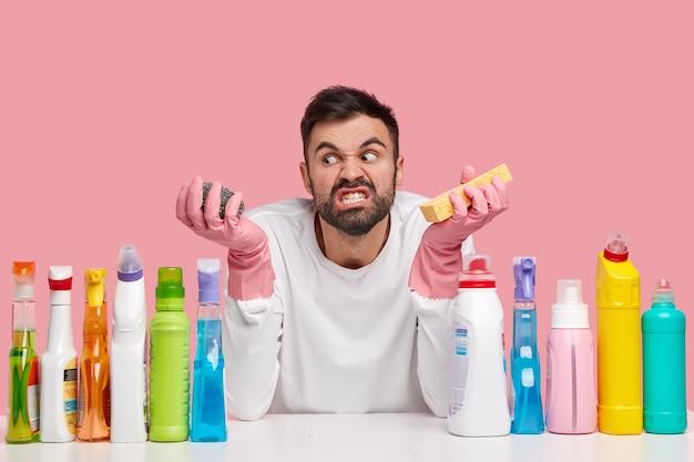 不満に悩まされている若い男の写真は怒って脇に見え、スポンジを持って、歯を食いしばって、多くの仕事にイライラしている