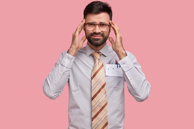 不満の写真無精ひげを生やした男性は頭痛に苦しみ、寺院に手を置き、悲しげな表情をして、オフィスでの仕事の後に疲れています