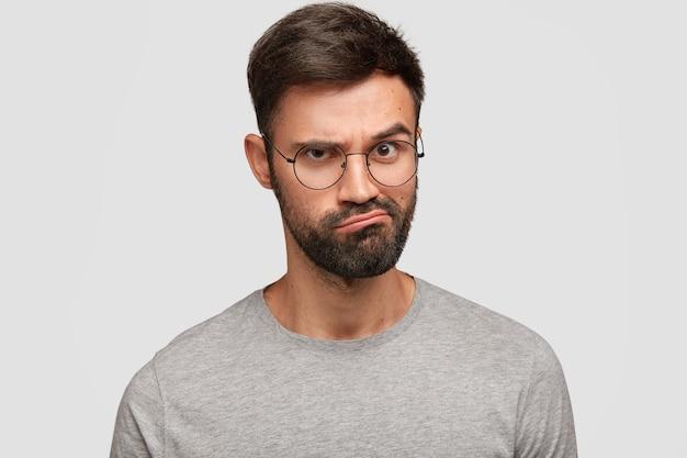 불만을 품지 않은 젊은 남성의 사진은 얼굴을 찌푸리고 입술을 찌푸리고, 불쾌한 표정을 짓고, 회색 티셔츠를 입고, 눈썹을 올리고, 흰 벽에 모델을 올립니다. 사람과 감정 개념