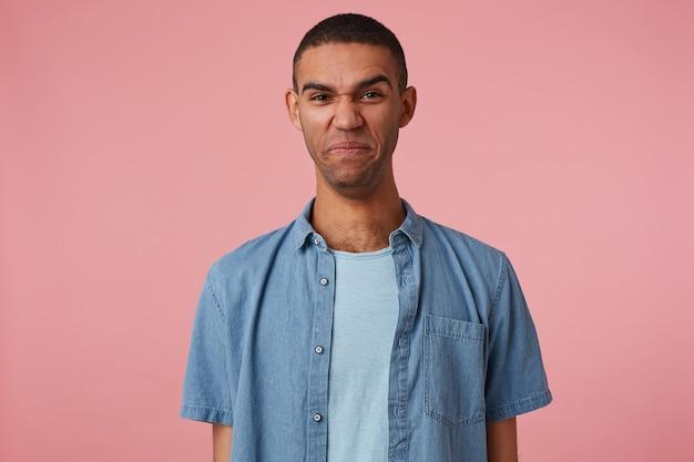 ピンクの背景の上に立っている、くしゃくしゃにした唇をした嫌な暗い肌の少年の写真。人と感情の概念。