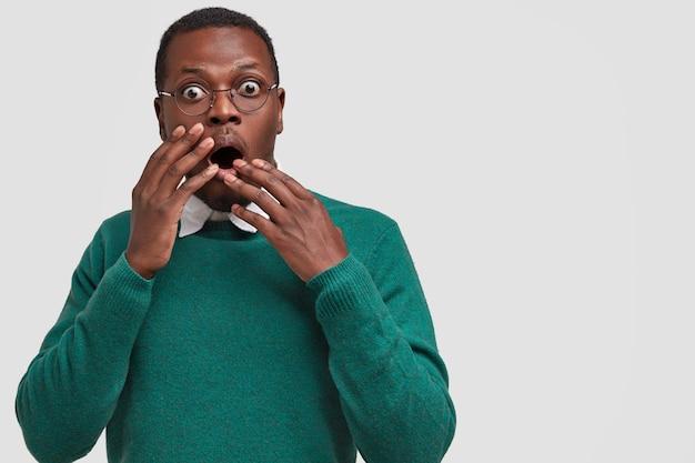 Фотография встревоженного испуганного черного хипстера прикрывает рот обеими руками, носит зеленую одежду