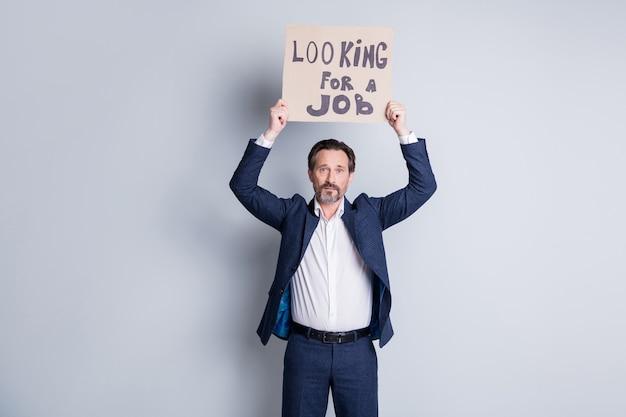 Фото уволенного пожилого зрелого парня, деловой человек, протестующий против финансового кризиса, краха компании, потерял работу, картонный плакат, забастовка на рынке труда, предприниматели, права, носить костюм, изолированный серый фон