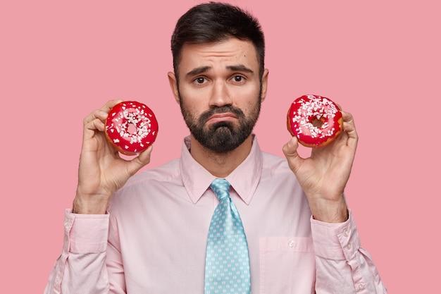 不機嫌なひげを生やした白人男性の写真は悲しい表情をしており、フォーマルな服を着た2つのドーナツを持っています