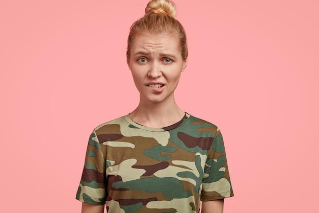 不機嫌な金髪の女性モデルの写真は、否定的な感情で見え、下唇を噛み、眉を上げ、心配と不満を感じ、カジュアルなtシャツを着て、ピンクの壁に隔離されています