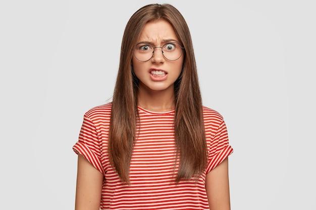 不機嫌な白人女性の写真は歯を食いしばり、イライラして顔をしかめます