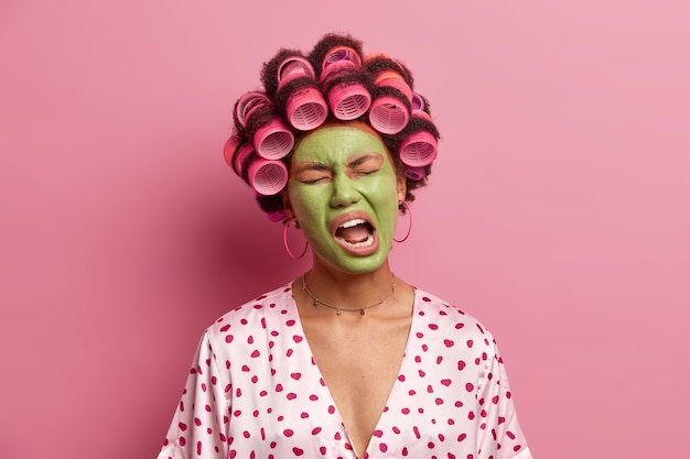 不機嫌な民族の女性の写真は、口を開けたまま、倦怠感を感じ、あくびをし、ピンクで隔離されたカジュアルな家庭服を着た緑色のマスクを適用します。フェイシャルトリートメントとウェルネスのコンセプト