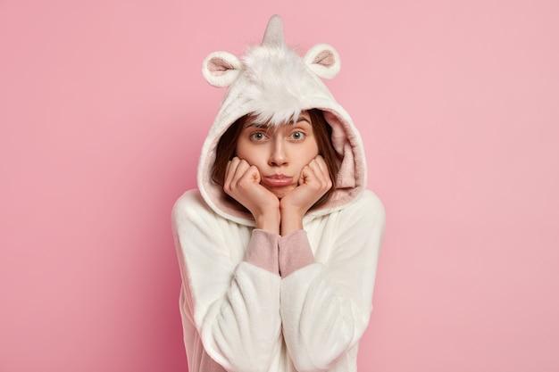 Фотография недовольной европейской женщины держит руки под подбородком, у нее угрюмый вид, она носит костюм кигуруми, чувствует себя одинокой, обиженной кем-то, изолированной за розовой стеной. несчастная девушка стоит в помещении