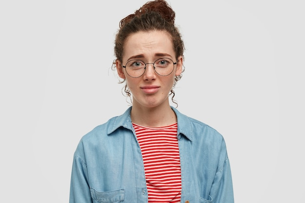 不機嫌なそばかすのあるヨーロッパの女性ティーンエイジャーの写真は、不幸な表情をしていて、彼女の新しい服が好きではなく、カジュアルなシャツと丸い眼鏡をかけ、白い壁に向かってポーズをとっています。顔の表情の概念