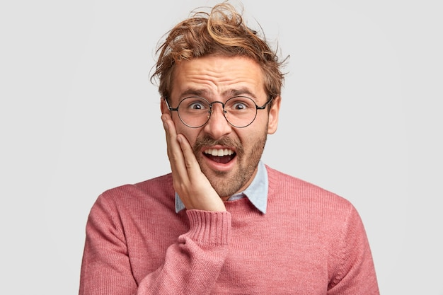 不機嫌な憤慨した白人男性の写真は不満に顔をしかめ、頬に手を保ち、不幸を感じ、巻き毛を持っています